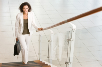 Smiling Young Businesswoman Walking Up Stairs